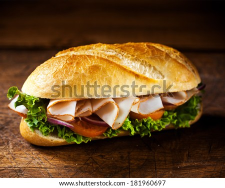 Fresh crusty golden roll with sliced ham and salad ingredients including lettuce, tomato and onion standing ready prepared for a tasty snack on a wooden table with copyspace - stock photo