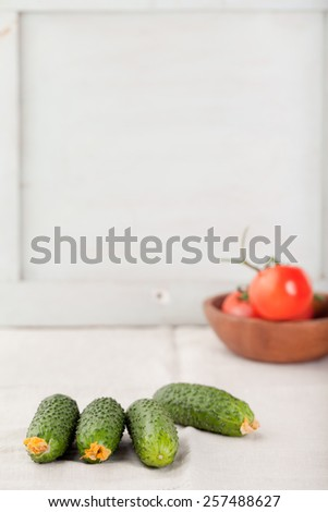 Fresh cucumbers and tomatoes on a white wooden background. Copy space. - stock photo