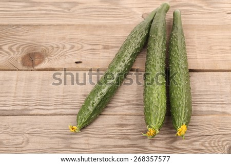 Fresh cucumbers on the wooden background - stock photo