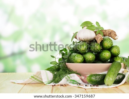 Fresh cucumbers prepared for preservation on the wooden table closeup - stock photo