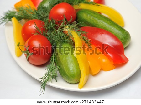 Fresh cucumbers, tomatoes, peppers and fennel on a plate. Horizontal frame. - stock photo