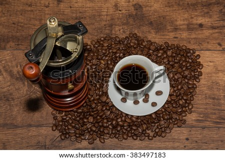 Fresh cup of arabica coffee with coffee beans and mill - stock photo