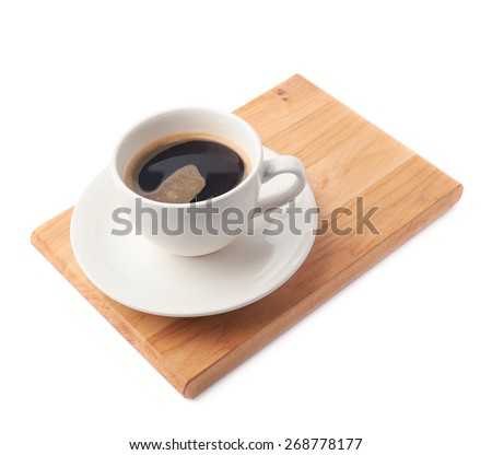 Fresh cup of coffee on a ceramic plate over the wooden serving board, composition isolated over the white background - stock photo
