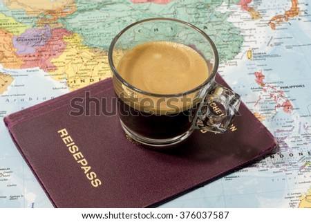 Fresh cup of coffee, passport and world map in a conceptual image of travel and tourism - stock photo