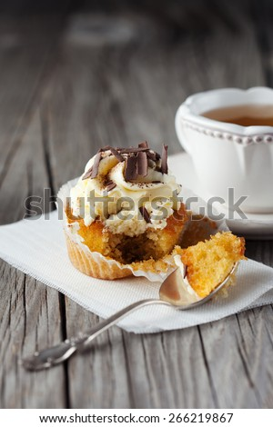 Fresh cupcake decorated with creamy vanilla cream and chocolate on old wooden background, selective focus - stock photo