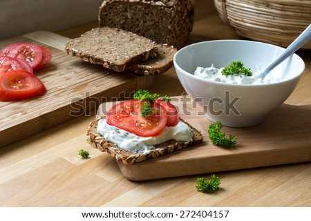 fresh curd cheese dip with herbs in a white bowl and rustic wholegrain bread with tomatoes on a kitchen board, healthy and powerful meal with natural food products - stock photo