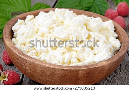 Fresh curd cheese in wooden bowl, close up view - stock photo