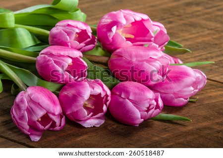 Fresh cut bundle of pink tulips on a wooden table - stock photo