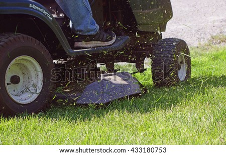 Fresh Cut Grass Flying From Riding Lawnmower - Person cutting long green grass with a riding lawn mower, close-up grass flying in the air while mowing the lawn, spring lawn care photo. - stock photo