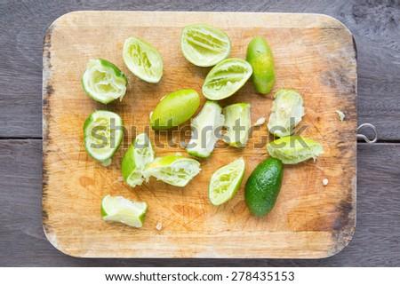 Fresh cut lime quarters - citrus fruit on wood block - stock photo