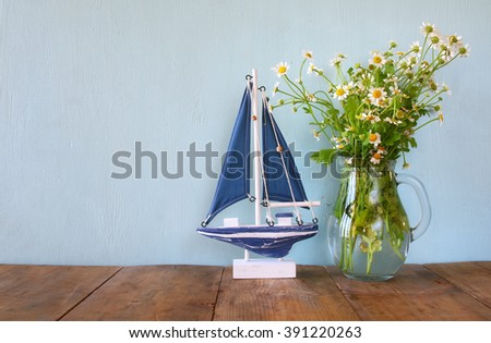 fresh daisy flowers next to wooden boat on wooden table. vintage filtered  - stock photo