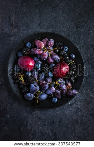 fresh dark fruits and berries on black background. Top view - stock photo