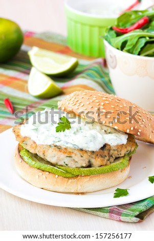 Fresh, delicious chicken burger in the Greek style with zucchini and yogurt cucumber sauce tzatziki - stock photo