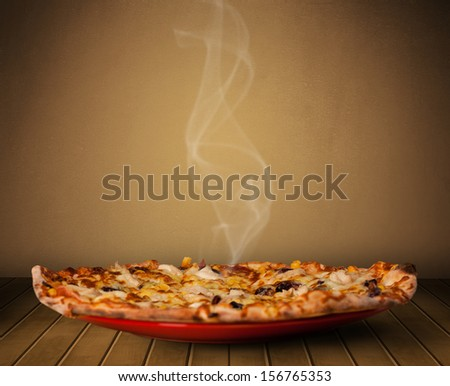 Fresh delicious home cooked pizza with steam on wood deck - stock photo