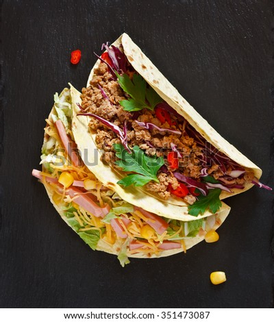 Fresh delicious mexican tacos on black. Street food. - stock photo