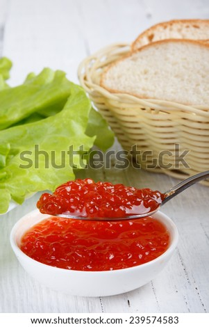 fresh delicious  red caviar  on an old wooden table - stock photo