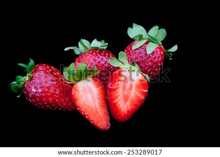 Fresh delicious red Strawberries on a black background. Strawberries are with green stems and leaves - stock photo