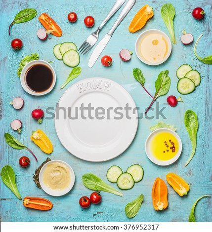 Fresh delicious salad and dressing ingredients around empty white plate on light blue background, top view, frame. Health salad making. Flat lay of healthy  lifestyle or detox diet food  concept - stock photo