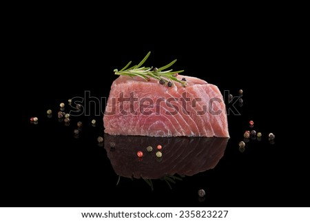 Fresh delicious tuna steak isolated on black background with colorful peppercorns. Sashimi sushi, healthy seafood eating.  - stock photo