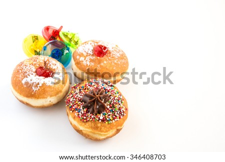 Fresh donuts and colorful dreidels for Hanukkah  Jewish Holiday.  - stock photo