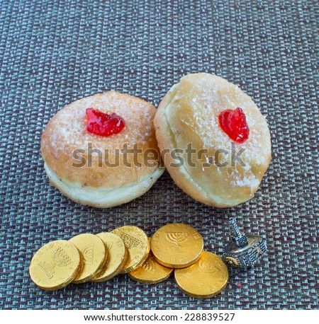 Fresh donuts, dreidel  and chocolate coins for Hanukkah celebration. - stock photo