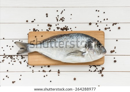 Fresh dorado fish on wooden cutting board with peppercorns - stock photo