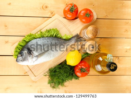 Fresh dorado on chopping board with lemon and vegetables on wooden table - stock photo
