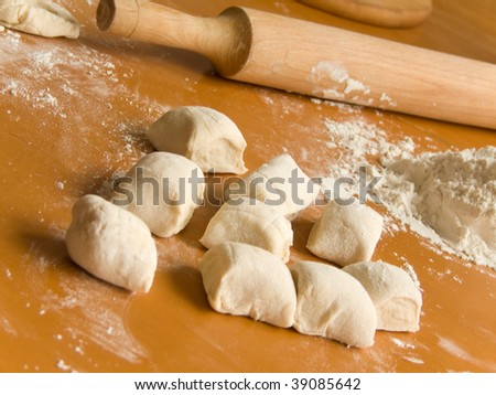 Fresh dough and rolling pin on the wooden table. Shallow DOF. - stock photo