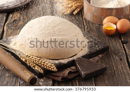Fresh dough for the preparation of homemade bread on a dark wooden table in a bakery closeup - stock photo