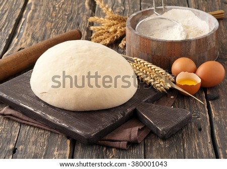 fresh dough on a wooden board on a wooden dark surface of the bakery - stock photo