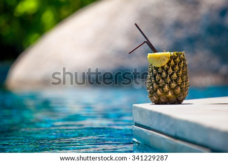 fresh drink in pineapple near the pool - stock photo