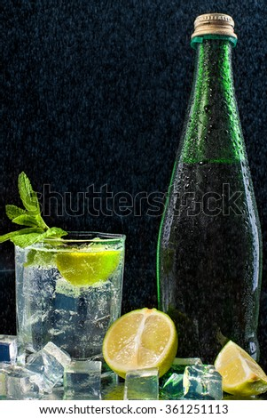 Fresh drink with splashes of water, green mint and lime on black background - stock photo