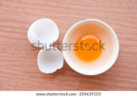 Fresh duck egg in cup on wood background - stock photo