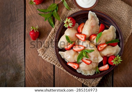 Fresh dumplings with strawberries and sour cream. Top view - stock photo