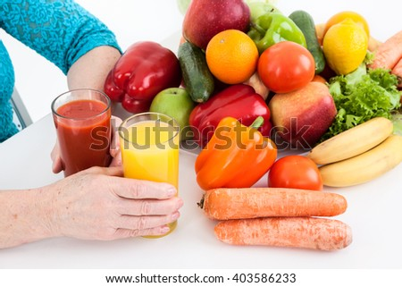Fresh ecological, natural products: vegetables, fruits and fresh juices are near arms of mature woman on a table - stock photo