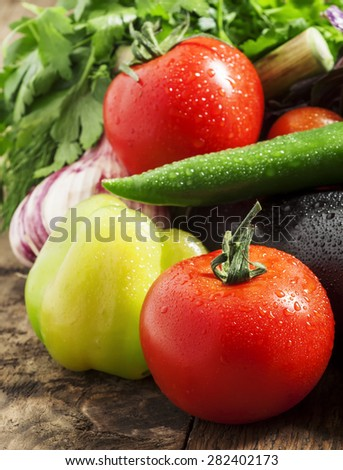 Fresh eggplant, tomatoes, peppers, zucchini, garlic and herbs on a wooden table, selective focus - stock photo