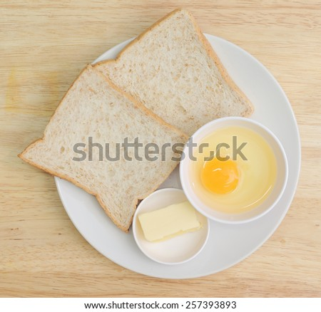 fresh eggs and bread with butter in dish - stock photo