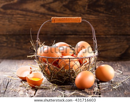 fresh eggs in a basket on wooden table - stock photo