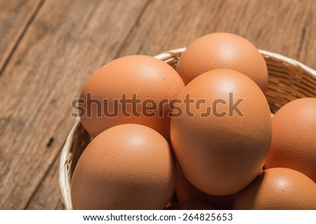 Fresh Eggs in basket on table close up. - stock photo