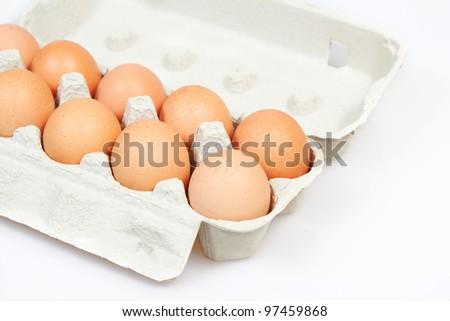 Fresh eggs in carton box on white background - stock photo