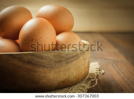 Fresh eggs in wood bowl on wood background , antique tone - stock photo