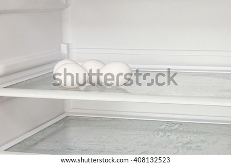 Fresh eggs on refrigerator shelf. - stock photo