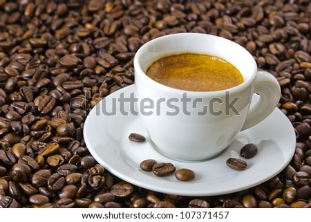fresh espresso in a white cup at roasted coffee beans - stock photo