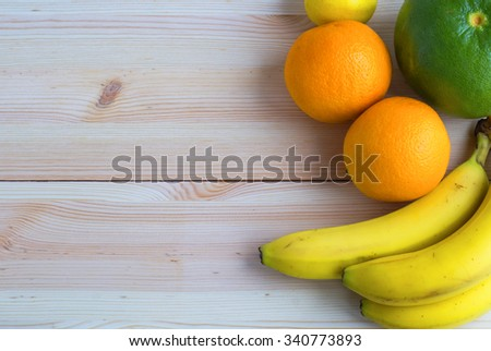 Fresh exotic fruits on wooden table background with copy space. Citrus fruit,  flat lay - stock photo