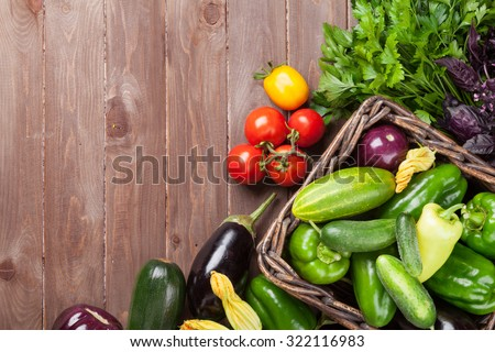 Fresh farmers garden vegetables and herbs on wooden table. Top view with copy space - stock photo