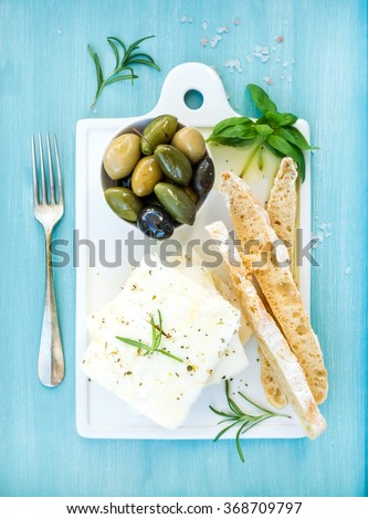 Fresh feta cheese with olives, basil, rosemary and bread slices on white ceramic serving board over bright turquoise blue painted wooden background, top view - stock photo