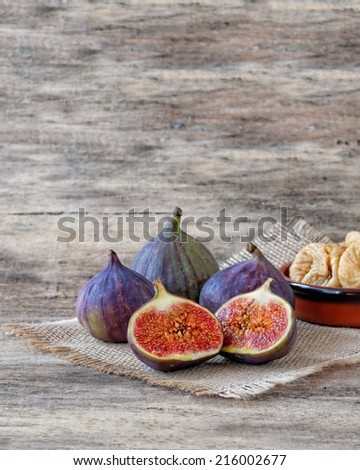Fresh figs cut in half with whole figs in the back - stock photo