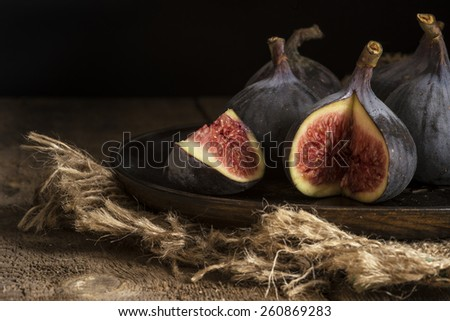 Fresh figs in moody natural lighting set with vintage style - stock photo