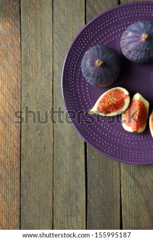 Fresh figs on the purple plate, food top view - stock photo