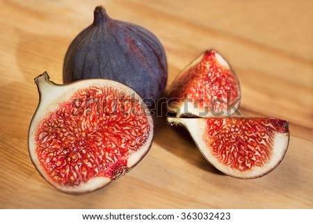 Fresh figs, whole and sliced on a light wood - stock photo